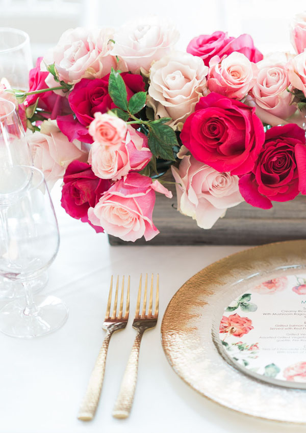 Pink flowers and floral plates on white table linens with gold accents