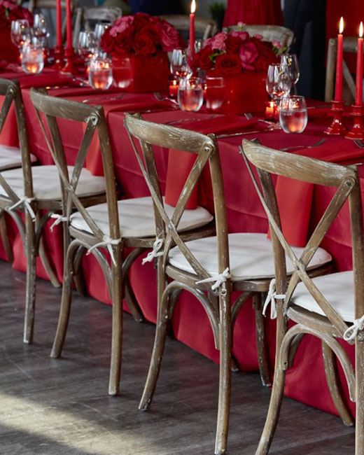 A photo of a table with wooden chairs and red table linens