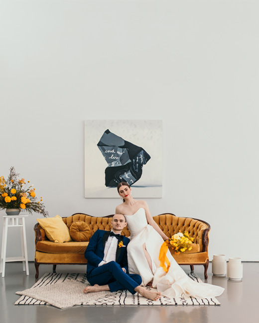 Bride and Groom sitting on a yellow vintage sofa